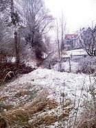 Late snow covers a meadow and brook bank.