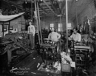 Letterpress printing - 1917 press room, using a line shaft power system. At right are several small platen jobbing presses, at left, a cylinder press.
