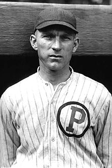 "A man wearing a dark cap and a pinstriped baseball jersey with a ""P"" inside a circle on the left breast."