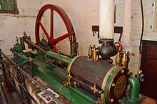 Green painted machinery with a horizontal shaft and wheel behind