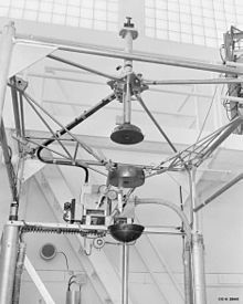 Complex scientific apparatus with metal frame surrounding three sections of a sphere held in the center by a system of rods, and separated vertically from one another so as to form a complete sphere when brought together