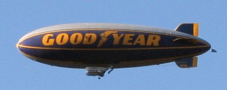 "Cigar-shaped blimp with ""Good Year"" written on its side."