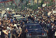 Deux hommes sortent par le toit d'une voiture se trouvant dans un convoi et saluent la foule dense présente le long du trajet.