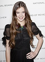 An image of a smiling light-skinned teenage girl with her hand on her hip. She has long light brown hair and is wearing a black top with sheer sleeves.
