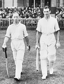 Two small men aged around 30 walk off the steps of a cricket ground pavilion onto the grass towards the centre of the playing area. Both wear light-coloured shirts, with rolled up sleeves, trousers and pads to protect their legs, all white. They wear batting gloves and hold a bat in readiness for play. The crowd sit behind a wooden fence; most are wearing suits and black cylindrical hats.
