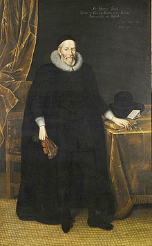 A tall elderly man with a beard, wearing long black robes and a large white ruff.  He is standing with a fan in his right hand and with his left hand resting on books on a table.
