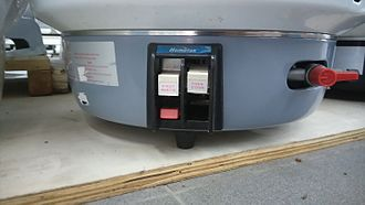 Rice cooker - A typical commercial gas cooker. To use it, the left lever is depressed to ignite the pilot burner for stand-by and keep-warm purposes. To start cooking, the right lever is pushed to operate the main burner, which is ignited by the pilot burner. Like its electric counterpart, the cook lever releases automatically once the rice is fully cooked.