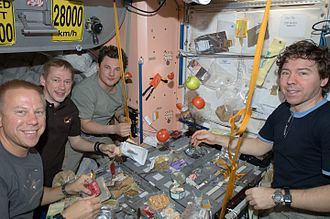 ISS-20 Crew members share a meal at a galley in the Unity node of the International Space Station.jpg