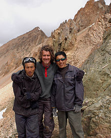 Three people stand outside facing the camera, mountaintops are in the backdrop, the tallest bearded Western man in the middle has his arms around the shoulders of two shorter Asian men.