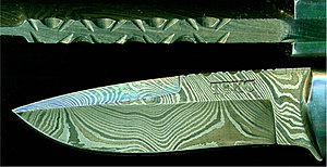 Pattern welding - A high resolution image of a modern pattern welded knife blade, showing the dramatic patterning on the side below, and the layering of the steel in the spine above.  Acid etching darkens the 1080 plain carbon steel more than it does the 15N20 low alloy nickel steel, producing alternating bands of light and dark on the surface.