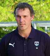 A photograph of a man with short greying hair wearing a navy blue polo shirt.
