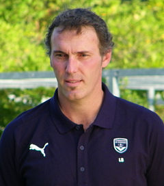 A middle aged man, wearing a dark blue top