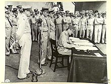 A large crowd of men in uniforms. Leclerc sits at a small desk signing a document. MacArthur stands behind him.