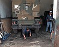 Local civilians working for Dynacorp repair a High-Mobility Multipurpose Wheeled Vehicle (HMMWV) in Sarajevo, Bosnia during Operation JOINT ENDEAVOR (the multi-national peace missio - DPLA - cb54f6e302a61dace6247691bf7dcfec.jpeg