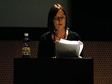 A woman standing on a podium, reading notes from a bunch of papers.