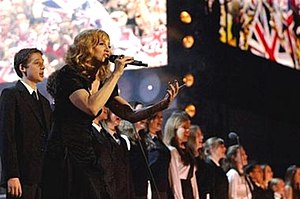 "Hey You (Madonna song) - Madonna performing ""Hey You"" on the concert. She is surrounded by a choir of children in school uniform."