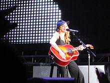 Image of a blonde woman sitting on a stool. She's wearing a black hat, black sleeveless shirt and black pants. She's holding an orange acoustic guitar in her hands. A microphone stands before her. Gray bright imagery can be seen in the background.
