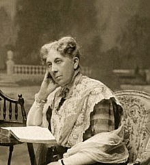 A sepia photograph showing the head and shoulders of a seated woman beside a small table on which is an open book