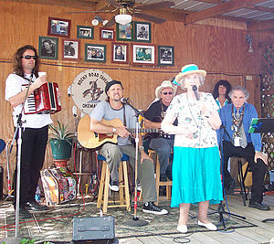 "Woody Guthrie Folk Festival - Mary Jo Guthrie Edgmon speaking at her ""pancake breakfast"" while (L-R) Radoslav Lorković, Jimmy LaFave, Joel Rafael, Marie Burns and David Amram look on. July 15, 2006."