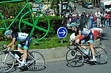 A pair of road racing cyclists in the team's black, white, and blue jersey, riding around a traffic island that features a large green sculpture of a bicycle. Spectators and motor vehicles are visible behind roadside barricades in the background.