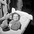 Meisje liggend in haar ledikantje met een speelgoedbeer, Bestanddeelnr 252-9354.jpg
