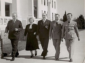 Women's suffrage in Australia - Robert Menzies (left) walking with early woman parliamentarian Enid Lyons (to his immediate right) in 1946. Menzies appointed Lyons as the first woman to sit in an Australian Cabinet in 1949.