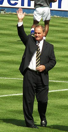 A man in a suit with his right hand raised, standing on a football pitch.