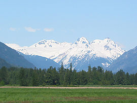 A large lightly glaciated mountain rising over a forested valley.