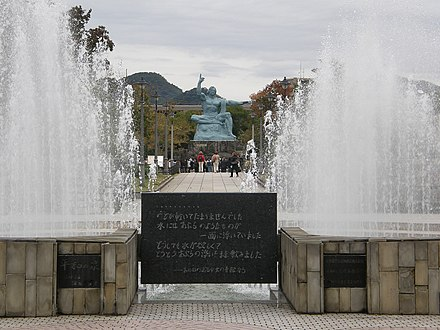 A plaque and the Peace Statue at the Nagasaki Peace Park Nagasaki Peace Statue - panoramio.jpg