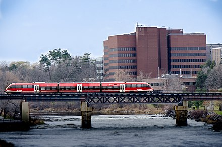 An O-Train crossing the Rideau River. The O-Train is a light rail public transportation service provided by OC Transpo. O Train 15773300606.jpg