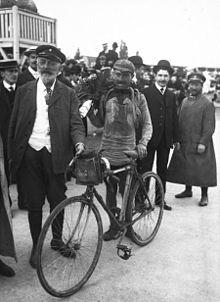 Photographie en noir et blanc montrant un cycliste couvert de boue à l'arrivée d'une course, entouré de plusieurs personnes.