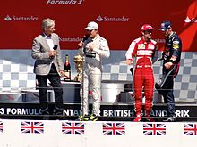 Damon Hill on a stage interviewing three drivers