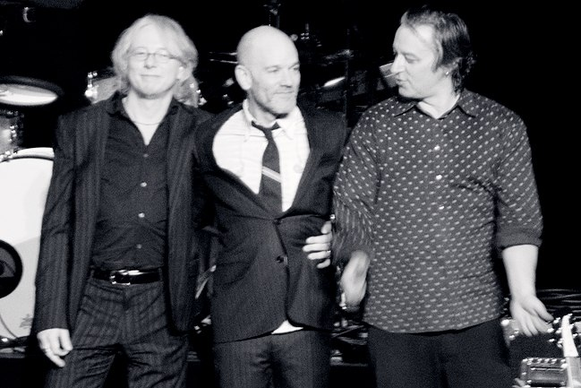 A black-and-white photo of the members of R.E.M. embracing and smiling onstage