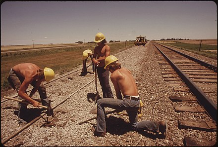 Rail track construction, Kansas, USA, 1974 RAILROAD WORK CREW IMPROVES THE TRACKS AND BED OF THE ATCHISON, TOPEKA AND SANTA FE RAILROAD NEAR BELLEFONT, KANSAS... - NARA - 556012.jpg