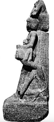 Standing man holding the hair of a man on his knees.