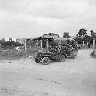 Operation Mallard - Riflemen of the 1st Battalion, Royal Ulster Rifles, of 6th Airlanding Brigade, aboard a jeep and trailer, driving off Landing Zone 'N'.