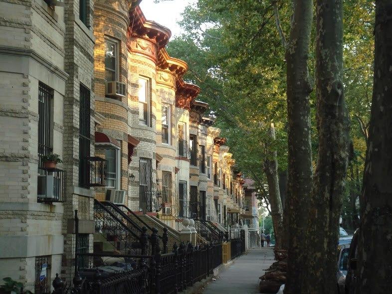 Row houses in alternating cream, yellow, and gray brick, in Bushwick, Brooklyn