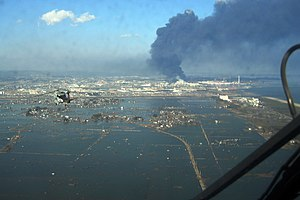 2011 Tōhoku earthquake and tsunami - An aerial view of the Sendai region with black smoke coming from the Nippon Oil refinery
