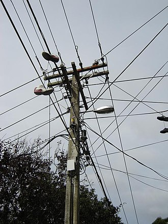 Utility pole - Utility pole supporting wires for electrical power distribution, coaxial cable for cable television, and telephone cable. A pair of shoes can be seen hanging from the wires (center-left, far right)