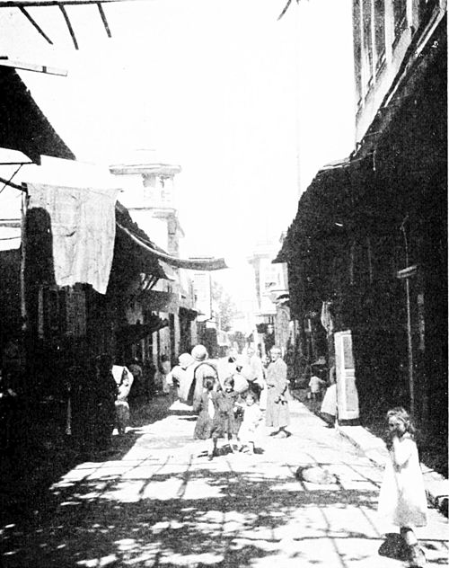 The street called Straight. Photo down a dirt street inhabited by children and adults. Single and double story buildings either side.