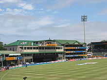 A view of a cricket field focusing towards the pavilion
