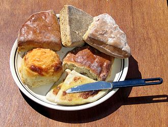 Scone - Clockwise from bottom: hot buttered tattie scones next to a cheese scone, shiny and flat treacle scones, and a milk scone above a fruit scone