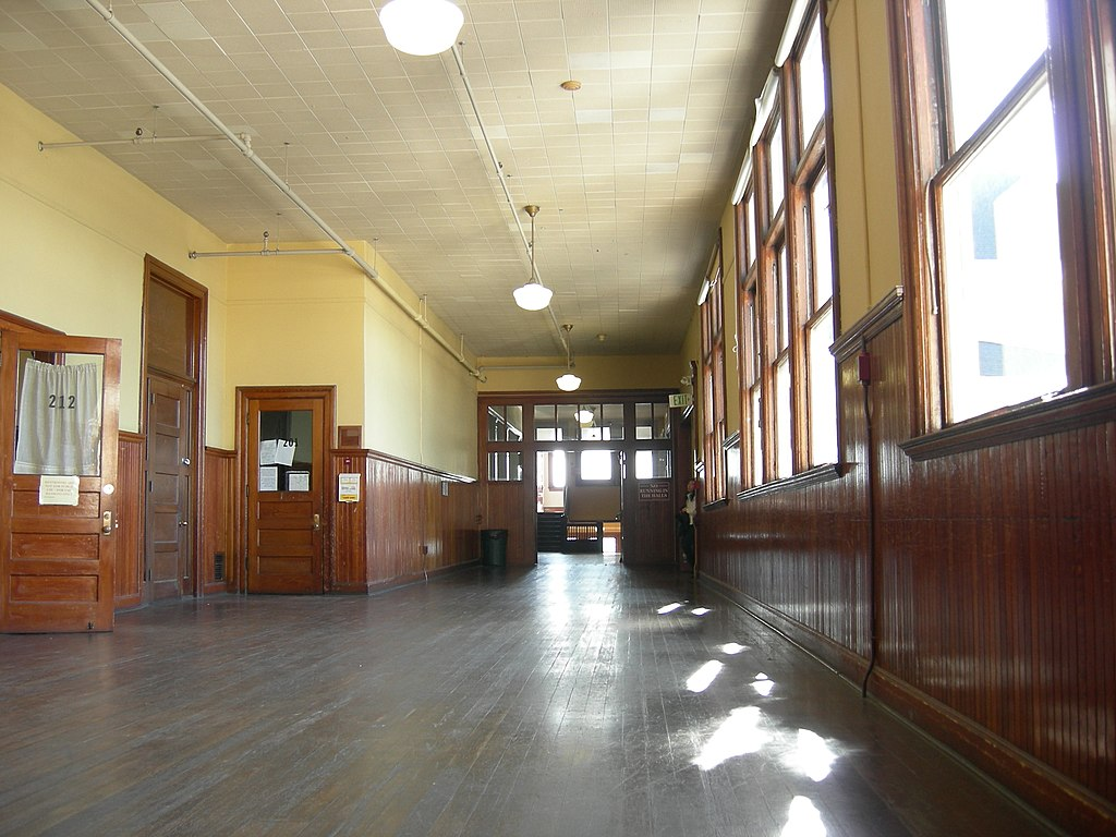 Wooden hallways of University Heights lined with sunlit windows
