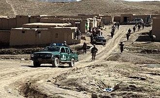 Kharwar District - Afghan National Police patrol through a bazaar while on their way into the village of Bakshikhala, Kherwar District, Logar Province