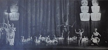 Wide angle shot of the whole stage showing the ballet scene; a threatening character stands at center with a raised sword, while other dancers lie prone on the stage appearing to plead with him; others stand at left looking concerned