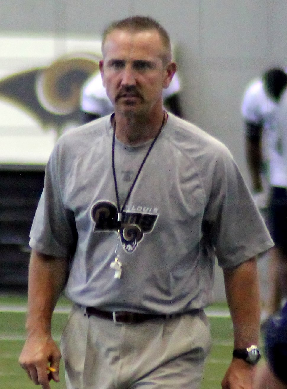Candid waist-up photography of Spagnuolo on the field in the St. Louis Rams indoor practice facility wearing a grey Rams t-shirt and khaki pants with a whistle hanging from a string around his neck