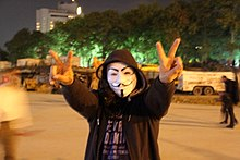 A protester wearing a Guy Fawkes mask.