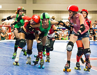 Roller derby - Lonestar Rollergirls in Austin, Texas, play on a banked track. This shows a Jammer (wearing the starred helmet cover) trying to pass a Pivot (wearing a striped cover) with various blockers assisting