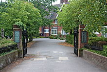 A gated entrance lined with trees leads to a red bricked building with white windows and a dark roof.