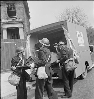 "London Ambulance Service - During a training exercise in Fulham in 1942, ambulance crew and civil defence workers place a ""casualty"" into an ambulance."